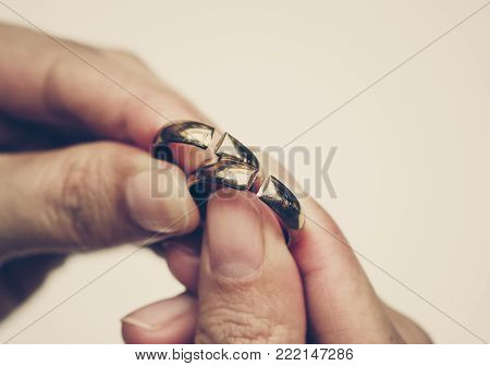 Hand holding broken rings / Divorce and ending relationship concept