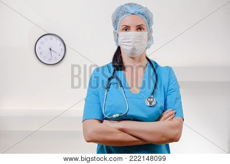 Medical doctor with stethoscope on white background. Female nurse wearing surgical mask and hat. Caucasian Woman Portrait.
