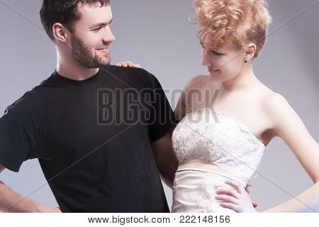 Relationships Concepts. Young Caucasian Couple Posing Together and Emnracing. Female Wearing Tailored Wedding Dress. Against Gray.Horizontal Image