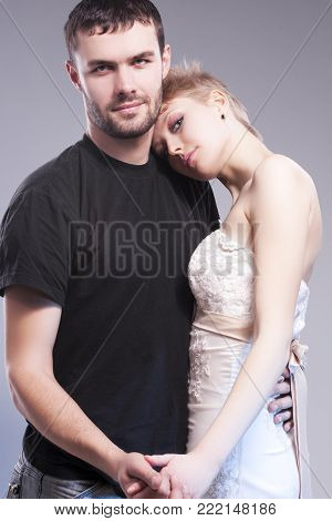 Relationships Ideas and Concepts. Playful Caucasian Couple Embracing Together. Blond Female Wearing Tailored Wedding Dress and Head Over the Man Shoulder. Against Gray.Vertical Composition