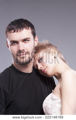 Relationships Ideas and Concepts. Playful Caucasian Couple Embracing Together. Blond Female Wearing Tailored Wedding Dress and Head Over the Man Shoulder. Against Gray.Vertical Shot