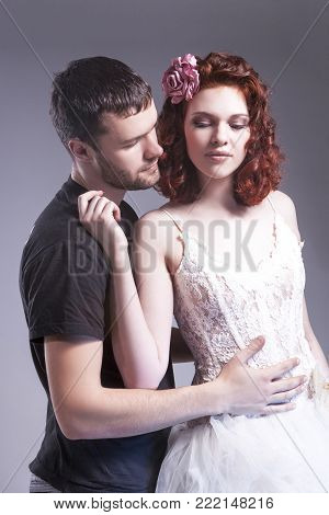Relationships Ideas. Sensual Caucasian Couple of Posing Embraced Together and Touching Each Other. Ginger Female Wearing Tailored Wedding Dress. Vertical Composition
