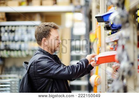 Middle age man choosing the right tool box in a hardware store. DIY concept
