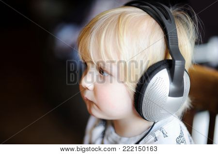 Cute toddler boy wearing big headphones listening to the music. Little child listening to kid's songs or developing audio at home. Technology, music or education concept.