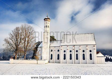 Beautiful St. Coloman pilgrimage church, located near famous Neuschwanstein castle, Bavaria, Germany (Deutschland) in snowy winter day