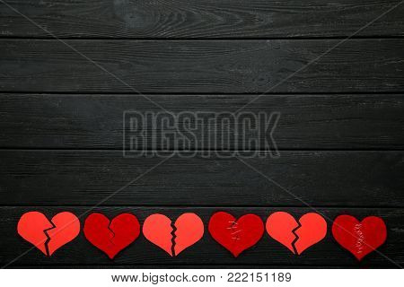 Broken red hearts on black wooden table