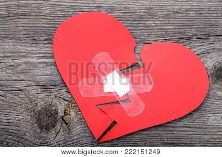 Red paper heart with adhesive bandage on wooden table