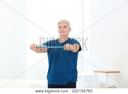 Senior man doing exercises with stretch band in rehabilitation centre