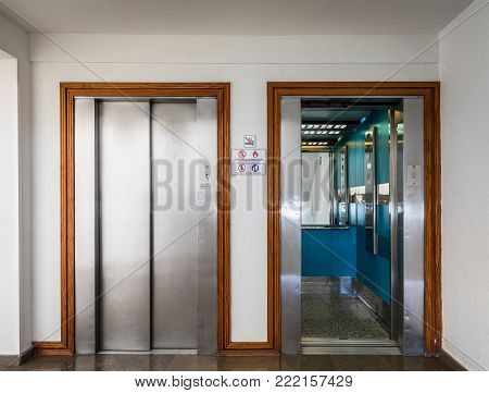 Open and closed chrome metal hotel building elevator doors realistic photo