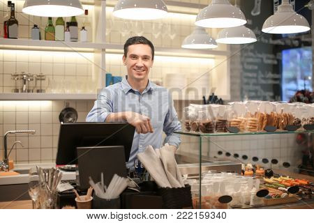 Young man standing in store. Small business owner portrait