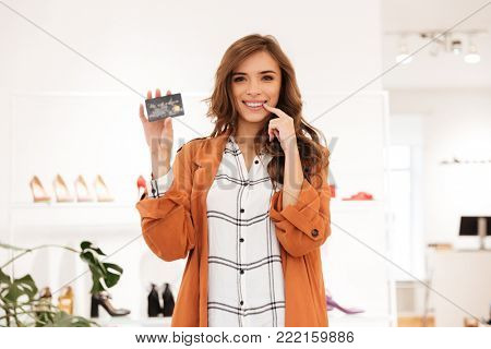 Portrait of an excited woman holding credit card while standing in a shoe boutique