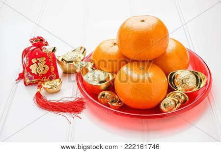 Chinese New year,ang pow red felt fabric bag with gold ingots and tangerine oranges with red tray on white wood table top,Chinese Language mean Happiness and on ingot mean wealthy poster