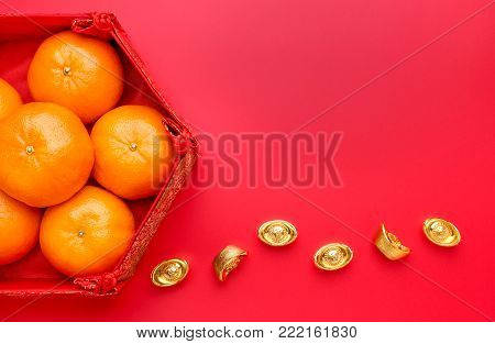 Group of orange tangerine in Chinese pattern tray with gold ingots on red table top. Chinese new year concep.Chinese Language ingot is wealthy