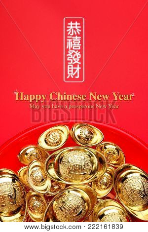 Top view group of golden ingots on red tray at red background.Chinese new year concept,leave space for adding text.Chinese Language on ingot mean wealthy and lable mean May you have a prosperous New Year