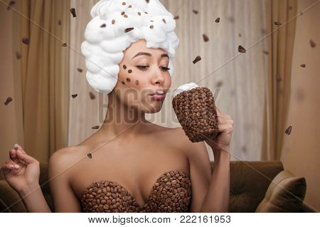 Creative portrait of beautiful funny woman with cup and dress in coffee beans