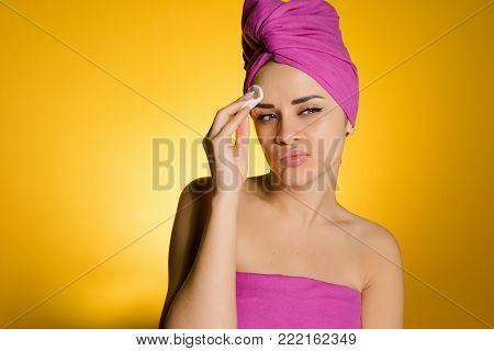 disgruntled young girl with a pink towel on her head cleans the skin with a cotton swab