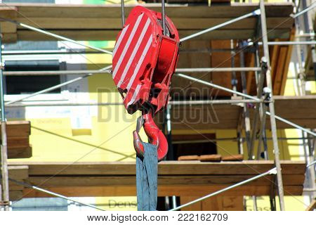 Red construction crane hook and crane box with yellow scaffolding background copy space.