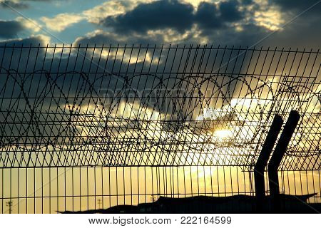 Airport safety fence over cloudy sky stock photo