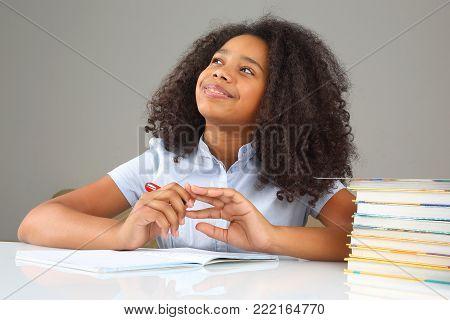 schoolgirl is thinking about school homework doing homework