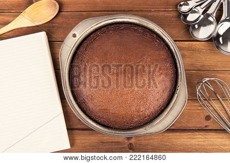 Freshly baked chocolate cake, cooking book and utensil disposed on wooden table. Top view.