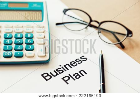 Working on business plan and calculating cost with pen and eye glasses. Closeup the word business plan on white paper. Concept of Starting A Business and Outlining Your Financing Needs.