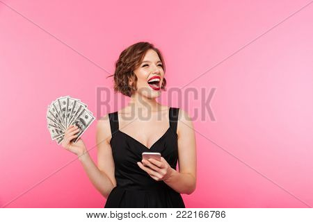 Portrait of an excited girl dressed in black dress holding bunch of money banknotes and mobile phone while looking away isolated over pink background