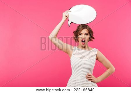 Portrait of an angry girl dressed in dress holding blank speech bubble above her head and looking at camera isolated over pink background