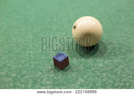 Billiard ball and chalk macro. On the green table cloth one ball and a piece of chalk for rubbing a sports stick for billiards