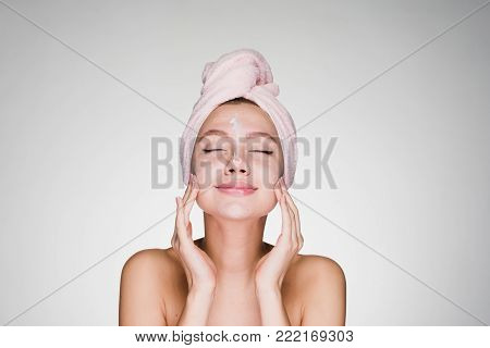 young attractive girl with a pink towel on her head puts a nourishing cream on her face, her eyes are closed