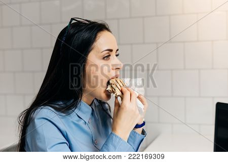 hungry young girl eagerly eats a sandwich in a cafe