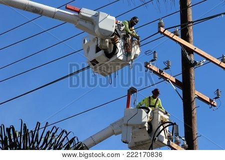 Two electricians in cranes fix electrical utility lines copy space blue sky.