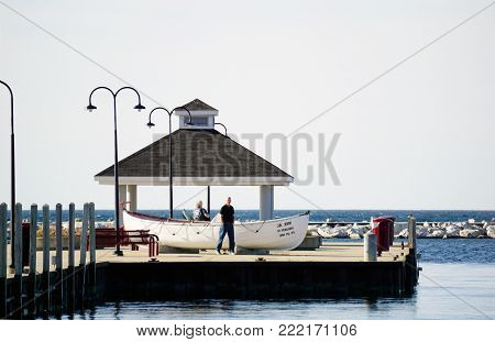 PETOSKEY, MICHIGAN / UNITED STATES - OCTOBER 18, 2017: A lifeboat, the J.B. John, and a gazebo, are at then end of Pier A, in the Petoskey Municipal Marina.