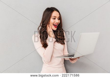 Portrait of satisfied and happy woman with red lips watching fascinating movie, using silver laptop in studio over gray wall