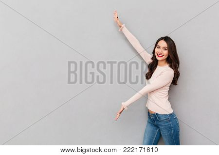 Image of pretty woman in casual showing something big with hands, demonstrating product or service over gray wall copy space