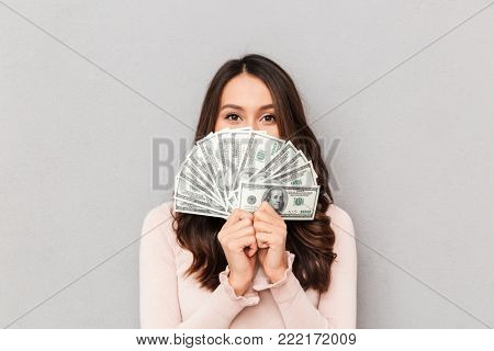 Image of lucky happy woman with long hair covering her face with fan of 100 dollar bills, having lots of cash money over gray wall close up