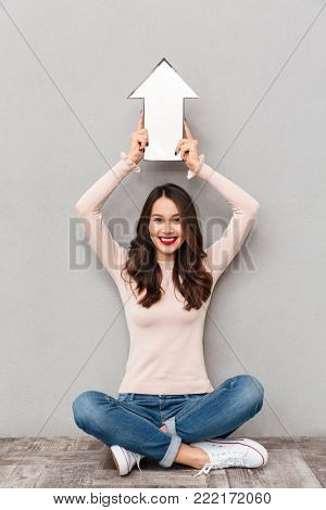 Portrait of attractive young woman holding paper arrow sign up above her head, while sitting legs crossed isolated over gray background