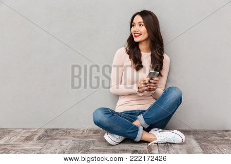 Portrait of smiling woman with red lips typing text message or scrolling in internet using mobile phone, sitting in lotus pose over gray background