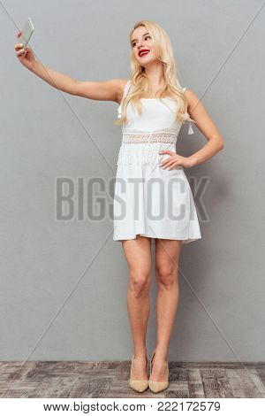 Full length portrait of an attractive woman taking a selfie whiel standing isolated over gray background