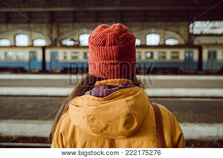 woman wiating for train on railway station in hat