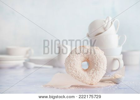 Donut with coconut topping on a light background with baking wax paper and porcelain cups and saucers. High key food photography. Stack of cups.