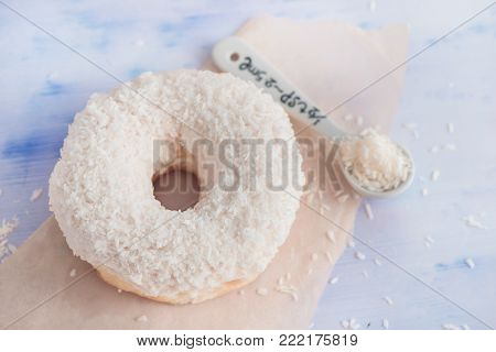 Close-up of a white donut with coconut topping on a light background. High key food photography.