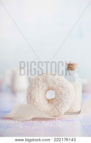 Coconut cream filled white donut with coconut topping on a light background. High key food photography. Bottle of coconut chips