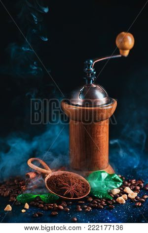 Roasted coffee beans with steam and coffee grinder on a dark background. Arabica leaves, brown sugar and anise stars as spices. Vintage still life with hot drink.