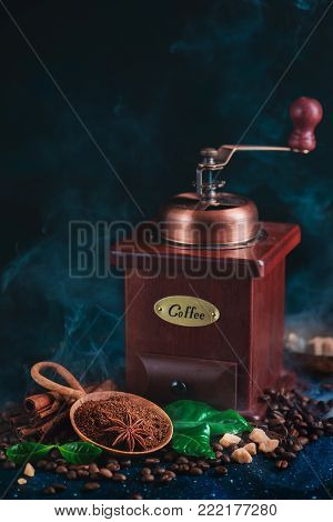 Coffee grinder with roasted coffee beans and steam on a dark background. Arabica leaves, brown sugar and anise stars as spices. Vintage still life with hot drink.