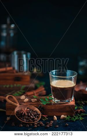 Espresso shot with foam on a wooden box with coffee beans, arabica leaves, cinnamon and spices on dark background. Brewing coffee in French press.