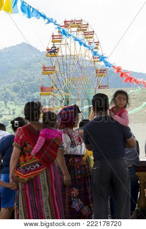 SAN JUAN OSTUNCALCO, GUATEMALA - JUNE 24: View of a ferrris wheel with unidentified people in colorful traditional clothing at the San Juan Ostuncalco fair in honor of Saint John the Baptist on June 24, 2017 in Guatemala.