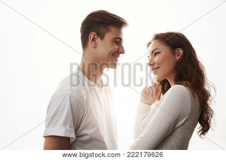 Sideways portrait of two adults in love. Guy flirts with beautiful girl trying to ask her for a date. He makes her smile. Every woman loves handsome boys with sense of humour. Relationship concept