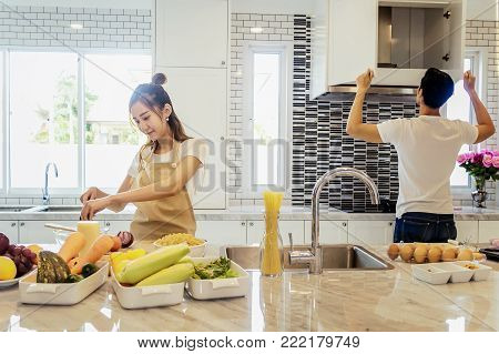 Beautiful asian young couple is looking to cooking in kitchen at home,Woman is mixing salad.