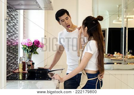 Beautiful asian young couple loving smiling are looking to cooking in kitchen at home,Happy woman feeding food to man.