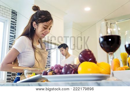 Beautiful asian young couple loving smiling are looking to cooking in kitchen at home,Woman is mixing salad.